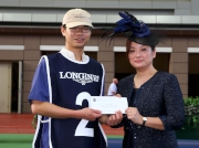 Before the race, Karen Au Yeung, Vice President of LONGINES HK, presents a HK$2,000 prize to the Stables Assistant responsible for Designs On Rome, the best turned out horse in the LONGINES Jockey Club Cup.