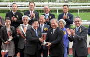 Kuok Hoi Sang, Vice Chairman & Managing Director of Chevalier International Holdings Limited, presents a trophy to winning trainer Dennis Yip.
