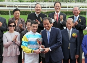 Tam Kwok Wing, Deputy Managing Director of Chevalier International Holdings Limited, presents a trophy to winning jockey Douglas Whyte.
