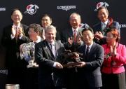 香港賽馬會董事鄭維志博士(右)頒發騎師駿馬銅像給浪琴表香港瓶冠軍「富林特郡」的馬主代表。