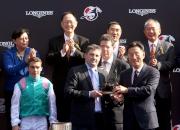 香港賽馬會董事鄭維志博士(右)頒發騎師駿馬銅像給浪琴表香港瓶冠軍「富林特郡」的練馬師代表。