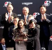 香港特別行政區民政事務局副局長許曉暉(右)頒發騎師駿馬銅像予浪琴表香港短途錦標冠軍「友瑩格」的馬主代表。