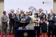 中央人民政府駐香港特別行政區聯絡辦公室副主任楊健(左),將國慶盃的獎盃頒發予勝出馬匹「新力風」的馬主黃良柏。