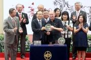 圖6, 7<br> 國慶盃頒獎儀式上,中央人民政府駐香港特別行政區聯絡辦公室副主任楊健(左)頒發銀碟予勝出馬匹「新力風」的練馬師約翰摩亞及騎師郭能。