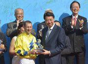 渣打銀行(香港)有限公司大中華及北亞地區行政總裁洪丕正(右)頒發紀念品予「明月千里」的騎師布文。
